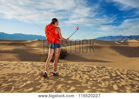 Woman with selfie stick take image in Death valley