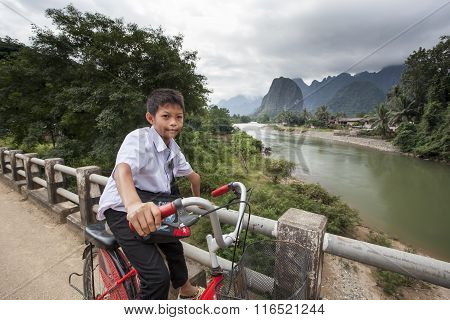 Young Unidentified Boy Cycling Back From School On A Wooden Bridge.