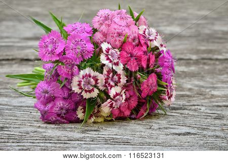 Bouquet Of Small Carnations On A Wooden Background