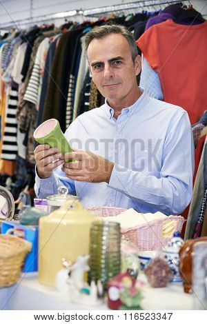 Male Shopper In Thrift Store Looking At Ornaments