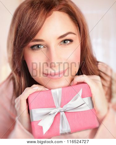 Closeup portrait of cute girl with pink gift box at home, receive present in Valentine day, happy romantic holiday