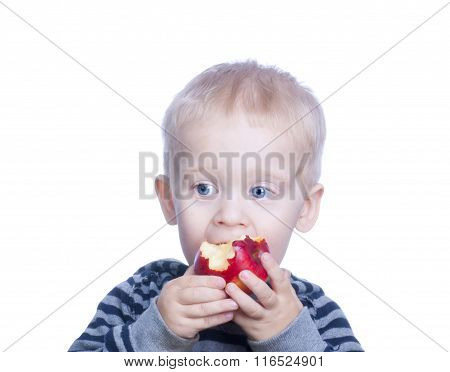 Beautiful Little Boy With Blond Hair And Blue Eyes Is Holding An Apple And Eats. The Child Eats Red