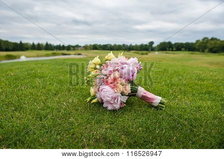 Bridal bouquet lies on a huge green lawn