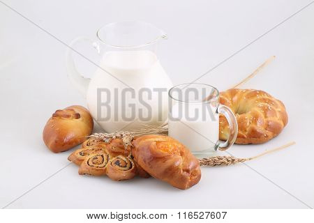 Rolls From Fancy Pastry And Milk In A Transparent Jug
