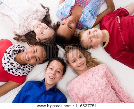 smiling children with different complexion lying head to head