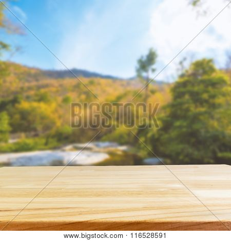 Wood Table And Blurry Forrest And Mountain In Background