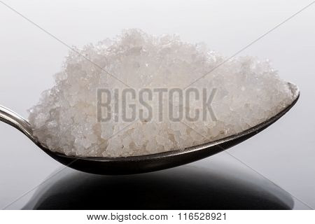 Sea coarse salt in spoon close-up. Side view.
