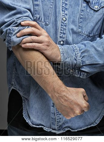 Man In Denim Shirt Rolling Up His Sleeves