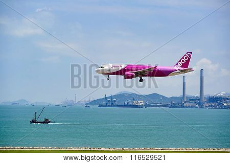 HONG KONG - JUNE 04, 2015: Peach aircraft landing at Hong Kong airport. Peach Aviation, operating under the brand name Peach is a low-cost airline based in Japan