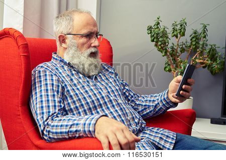 senior man resting on the chair and looking at hid smartphone at home