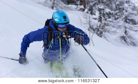 extreme freeride skier skiing on fresh powder snow in forest downhill at winter season
