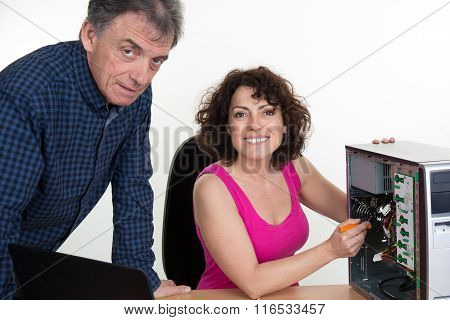 Woman Fixing A Computer While A Man Is Looking At The Camera