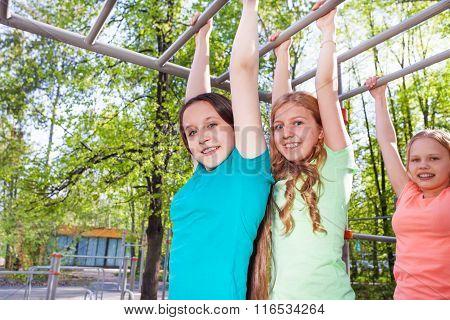 Three beautiful girls hanging on brachiating bar