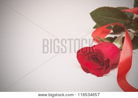 Red Rose With Ribbon On A Light Wooden Background. Women' S Day, Valentines Day, Mothers Day