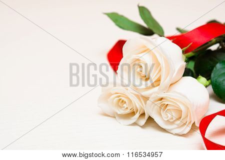 White Roses With Red Ribbon On A Light Wooden Background. Women' S Day, Valentines Day, Mothers Day