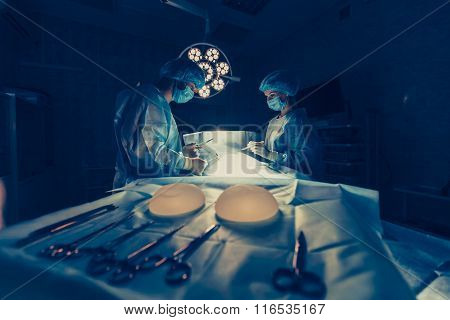 Surgeons team working with Monitoring of patient in surgical operating room. breast augmentation