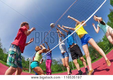 Teenagers playing volleyball on the game court