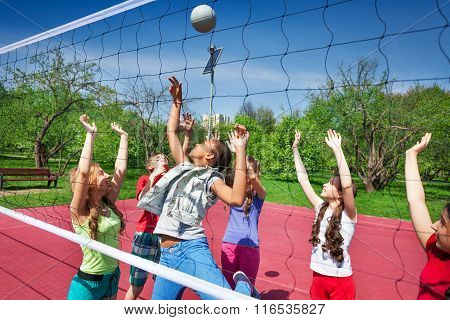 View through volleyball net of playing teens
