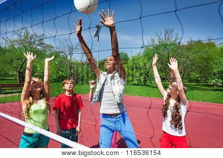 View through volleyball net of playing children
