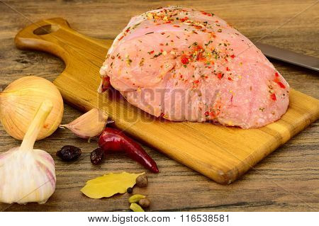A Piece of Raw Turkey in Spices for Grilling on Woody Background