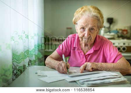 An elderly woman fills in utility bills.