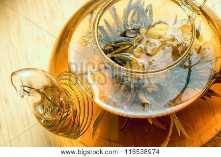 Flowering Tea In Glass Teapot On Rustic Wooden Background, Top Close Up View