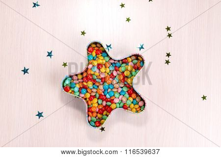 colorful round candies are in the box in the shape of a star