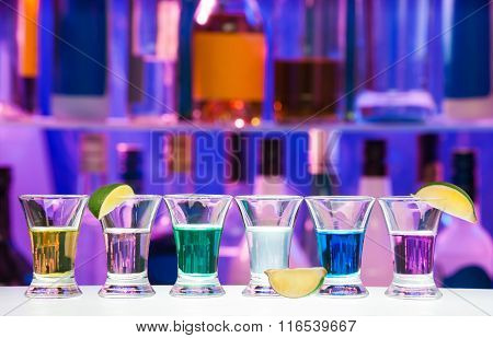 Shot glasses with lime in row, bar bottles on back