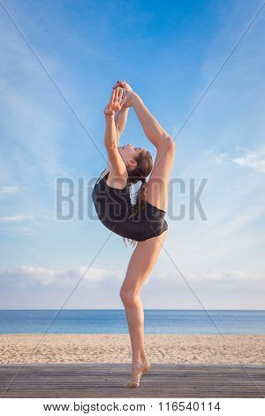 fit healthy young dancer doing stretching pose