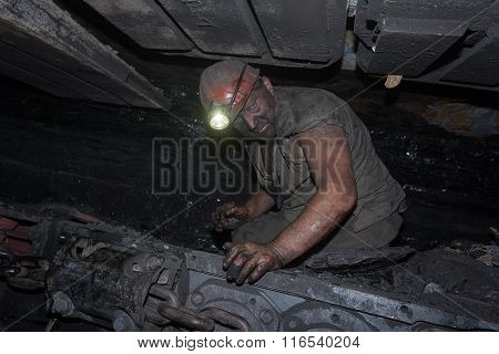 Donetsk Ukraine - August 16 2013: Miner repairs coal combine on the job in mines. Mine name Chelyusk
