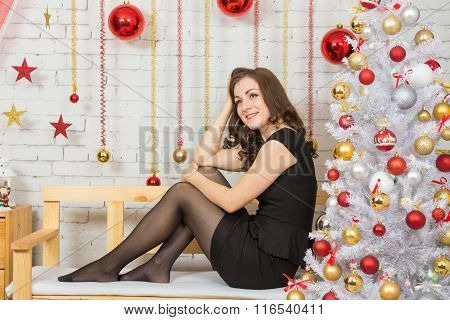Happy Young Girl Sitting On A Bench In A New Years Interior