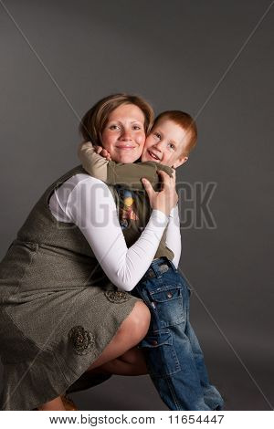 little boy gently embrace pregnant mother