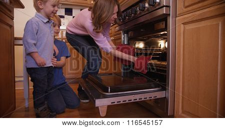 Beautiful White Mother Using Oven Mitts To Remove Cookie Tray