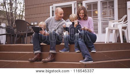 Beautiful Family Looking At Handheld Devices Outside