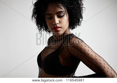 Woman With A Short Afro Hair On A Grey Bakground