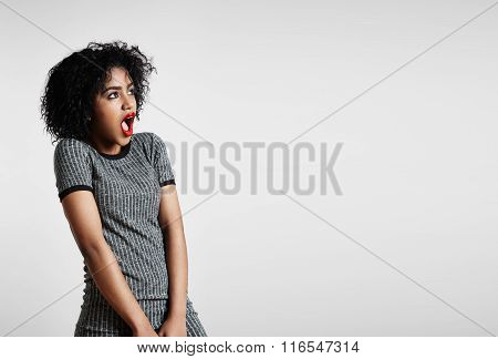 Shocked Woman With An Open Mouth Looking Aside On A Background
