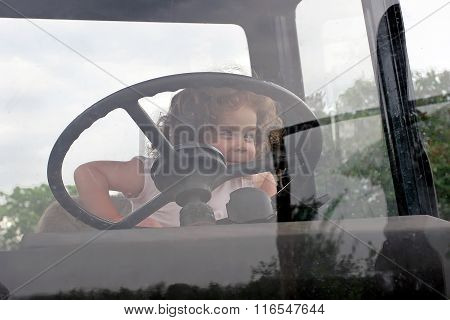 Little Curly Girl Emotionally Hold On To The Steering Wheel In The Tractor Cab