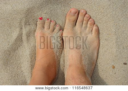 Feet Of Father And His Teen Daughter On The Sand
