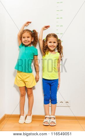 Two little girls standing close to the scale on the wall showing height with hand above the head with crop in full height portrait