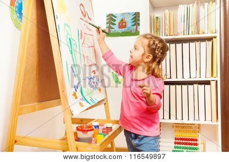 Child painting landscape picture on easel