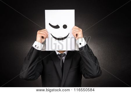 Businessman holding blinking emoji