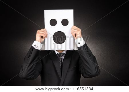 Businessman holding confused emoji