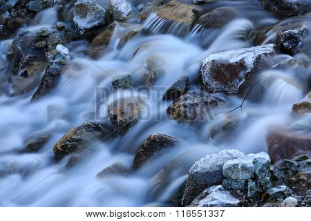frozen stones in run of mountain river at winter time