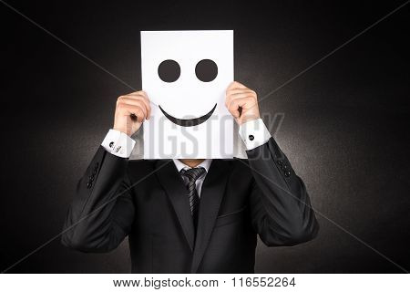 Businessman holding paper with smiley face