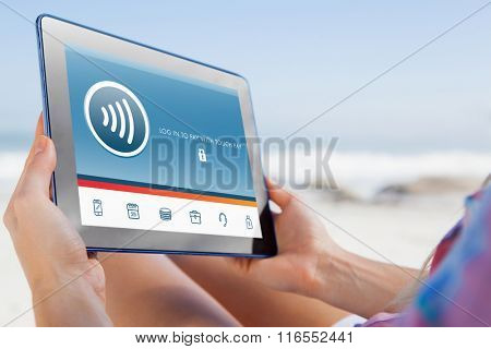 Woman sitting on beach in deck chair using tablet pc against web