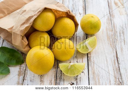 Freshly Lemons In Paper Bag On White Wooden Table