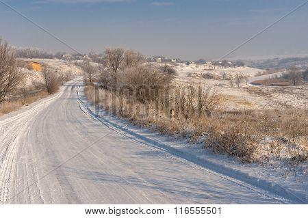 Winter landscape with country road leading to Novo-Nikolaevka village in Dnepropetrovskaya oblast Uk