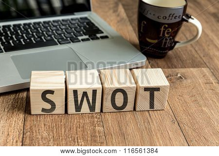 SWOT written on a wooden cube in a office desk