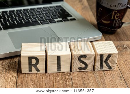 Risk written on a wooden cube in a office desk