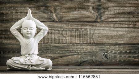 Sitting Buddha. White Monk Statue On Wooden Background